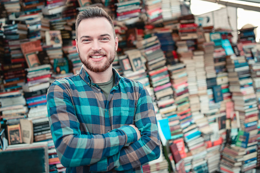 Smiling Male Selling Books at Outdoors Bookstore in Town Square