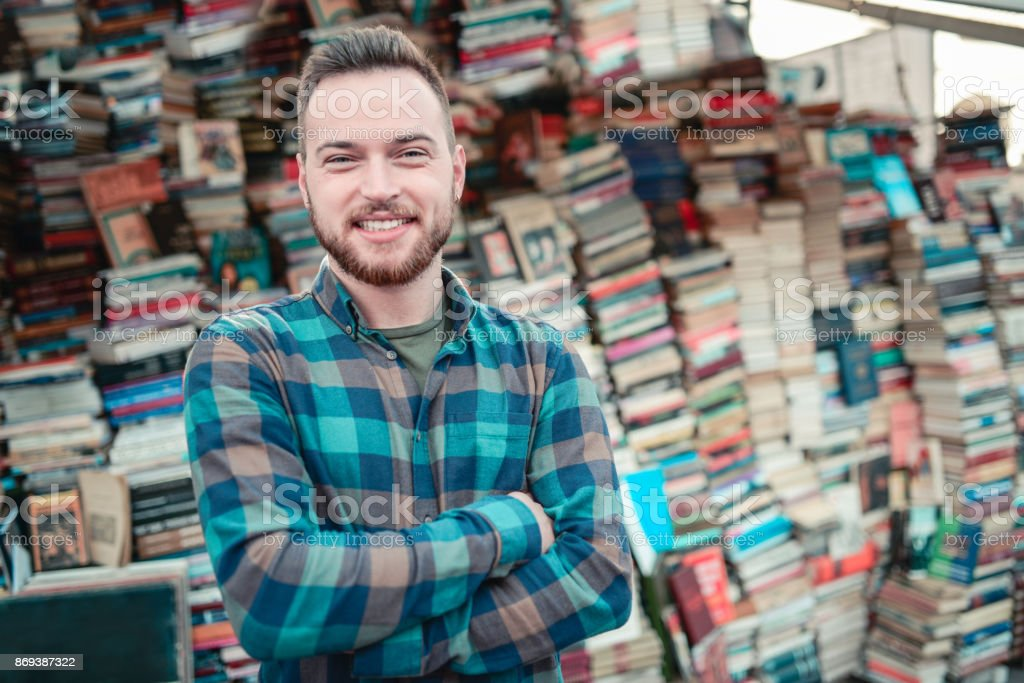 Smiling Male Selling Books at Outdoors Bookstore in Town Square stock photo