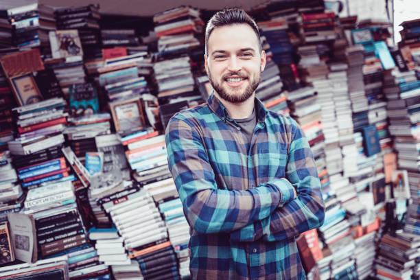 lächelnd männlichen verkaufen bücher in freien buchhandlung im altstädter ring - gebrauchte bücher verkaufen stock-fotos und bilder