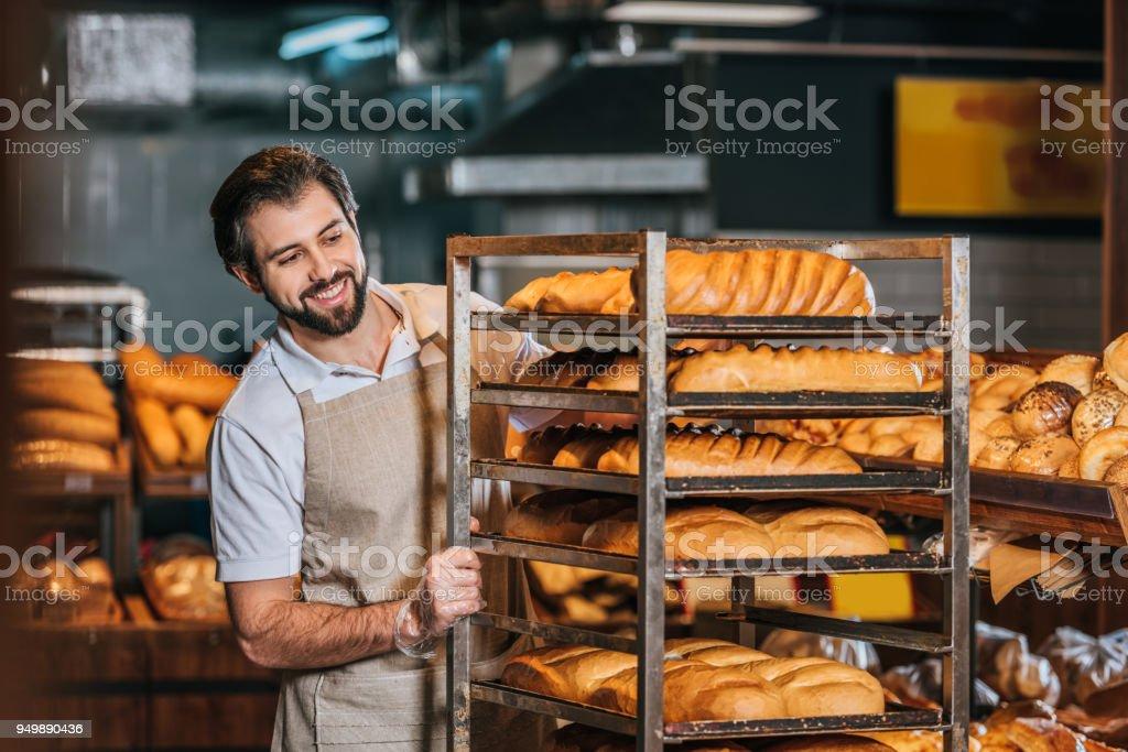 smiling male shop assistant arranging fresh pastry in supermarket - fotografia de stock