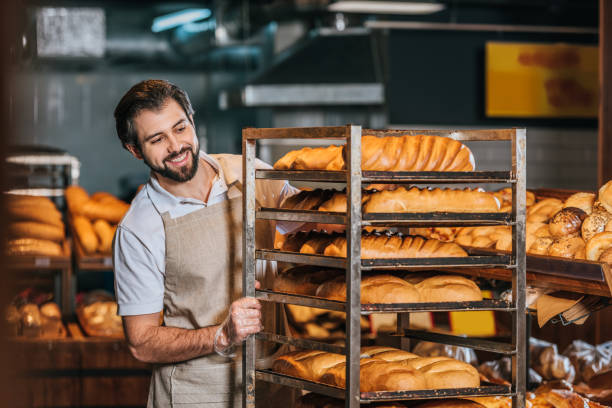 smiling male shop assistant arranging fresh pastry in supermarket stock photo
