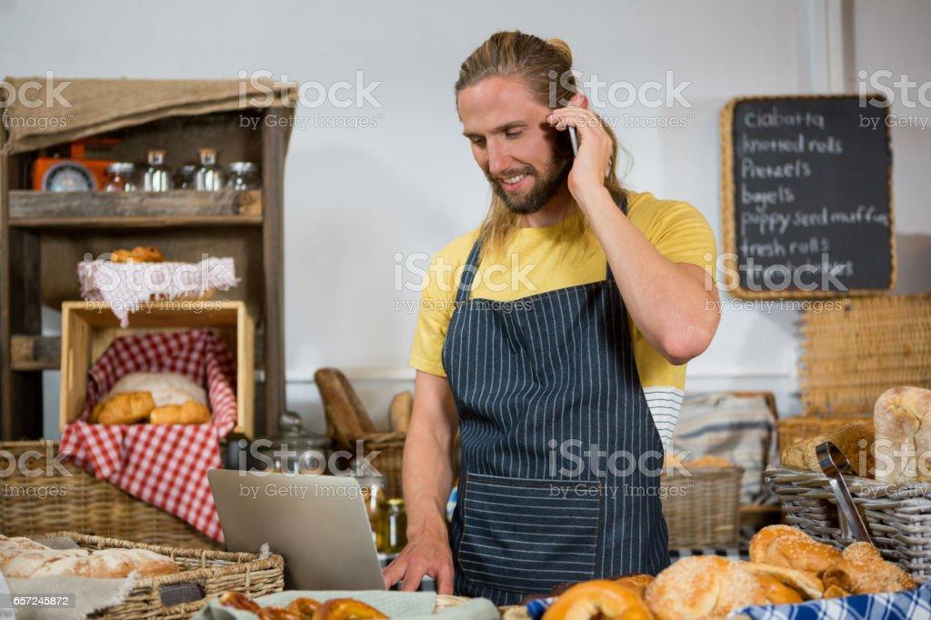 Smiling male staff talking on mobile phone while working on laptop at counter stock photo