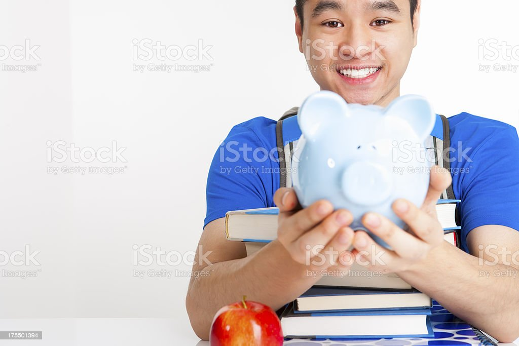 Smiling male student holding piggy bank stock photo