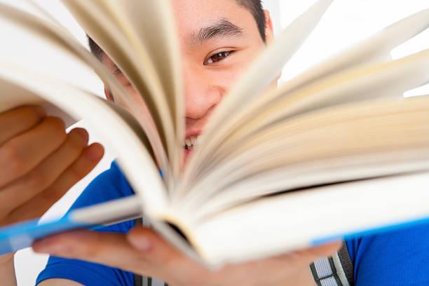 lächelnd männlich schüler blättern - schnell lesen lernen stock-fotos und bilder