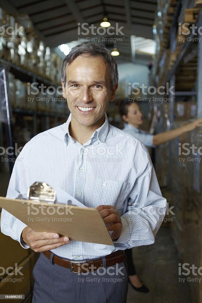 Smiling male supervisor working at warehouse royalty-free stock photo