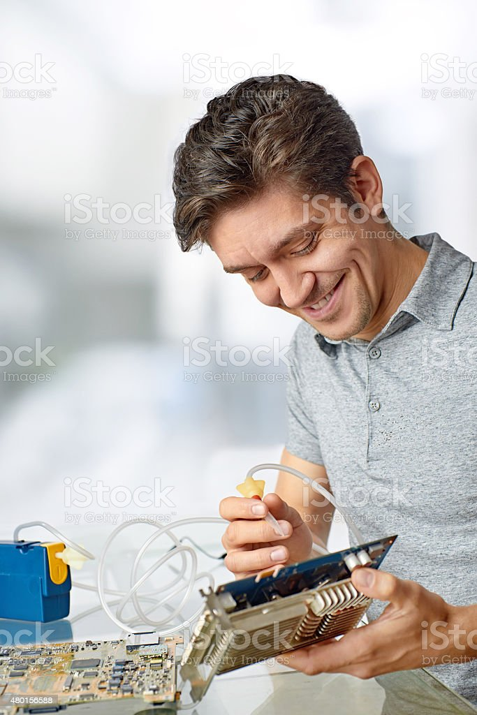 Smiling male tech cleans faulty computer processor stock photo
