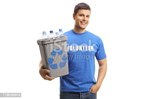 Smiling male volunteer holding a plastic recycling bin with bottles and posing isolated on white background
