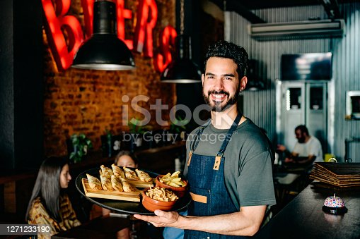Hispanic male waiter pausing to smile at camera while delivering tray of empanadas and other snacks at Buenos Aires restaurant.