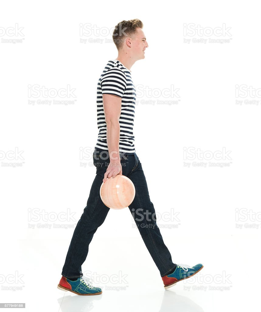 Smiling male walking with bowling ball stock photo
