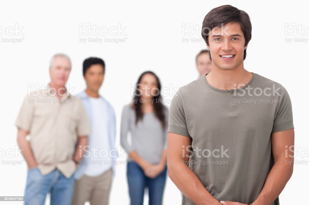 Smiling male with friends behind him stock photo