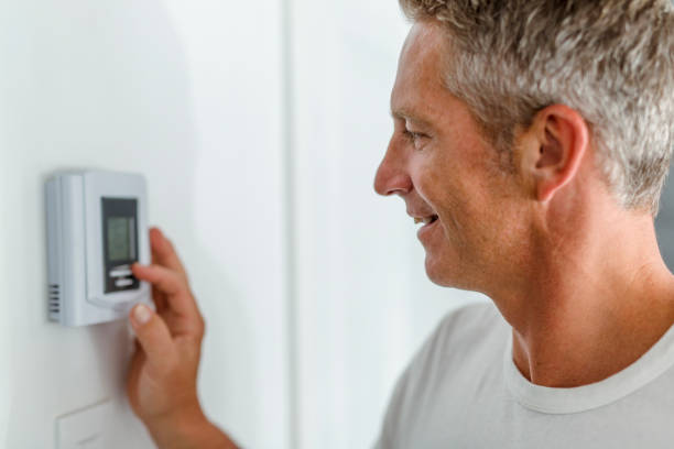 Smiling Man Adjusting Thermostat On Home Heating System stock photo