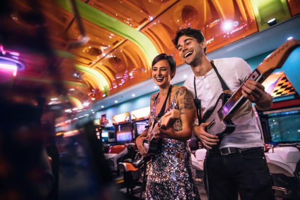 lächelnder mann und frau das gitarre-spiel auf einer spiele-arcade - arkade stock-fotos und bilder