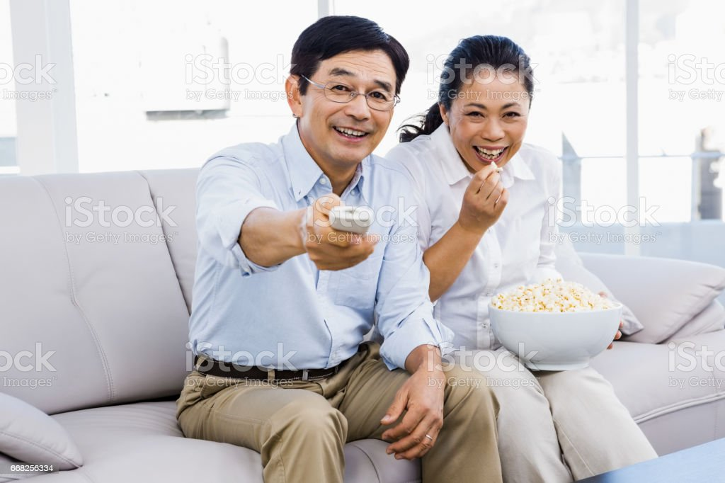 Smiling man and woman sitting on couch foto stock royalty-free