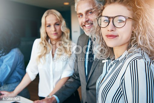 istock Smiling man and women looking at camera in office 870891304