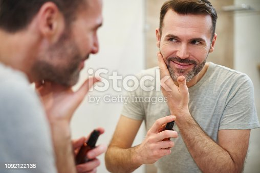 Smiling man applying beauty product on his face