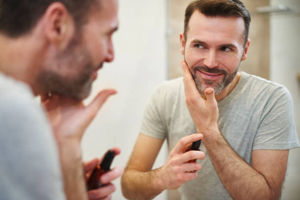 smiling man applying beauty product on his face - beard stock pictures, royalty-free photos & images