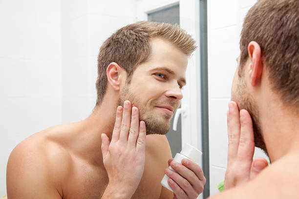 Smiling man applying cleanser to face stock photo