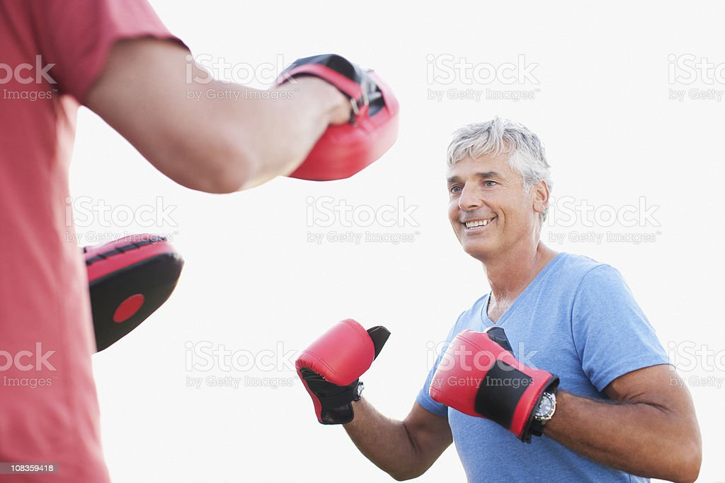 Smiling man boxing with sparing partner royalty-free stock photo