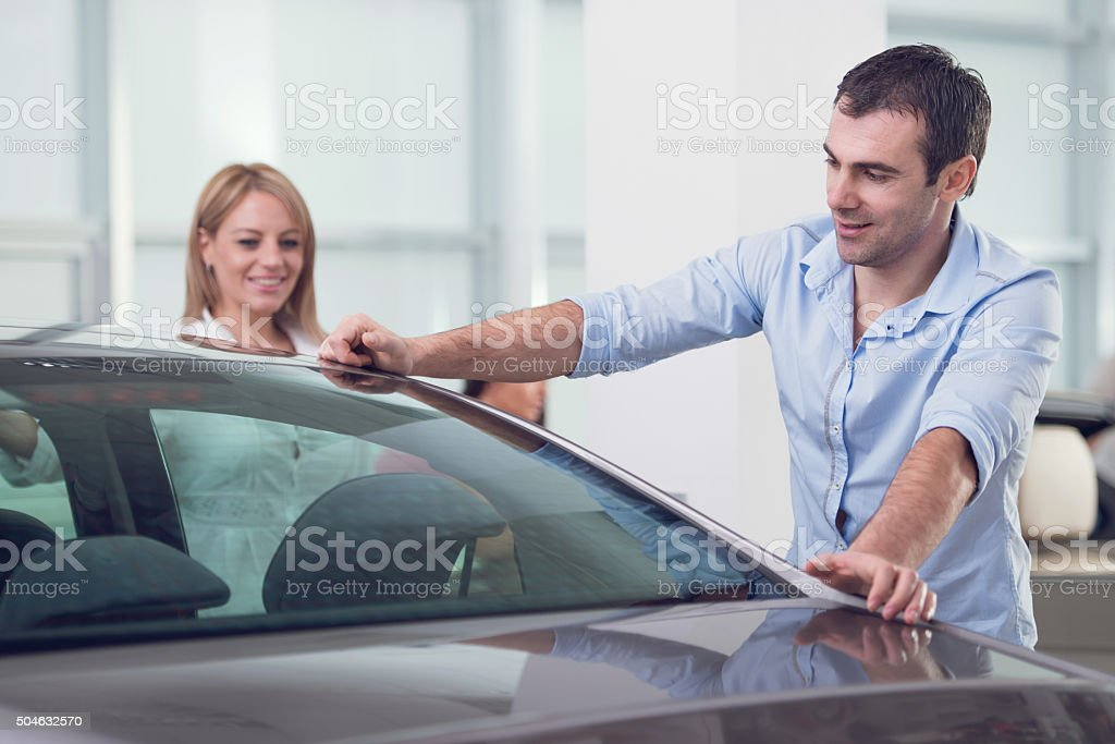 Smiling man buying a new car with his wife. stock photo