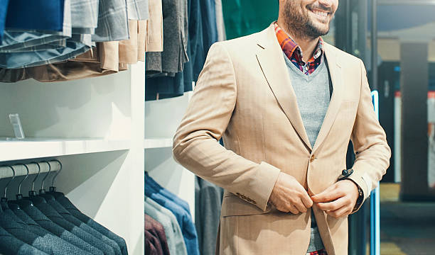 smiling man buying some clothes at department store. - preppy fashion stock photos and pictures