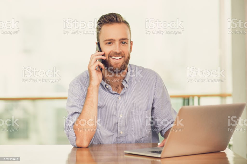 Smiling Man Calling on Phone and Working on Laptop royalty-free stock photo