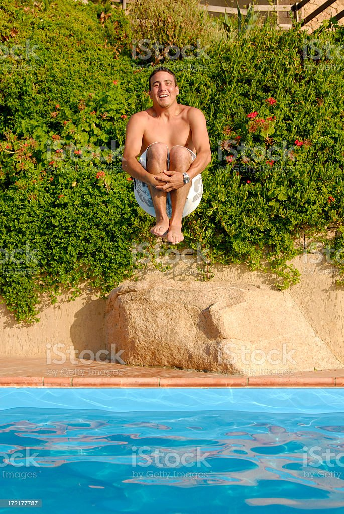 Smiling man cannonball jumps into pool, with bush behind royalty-free stock photo