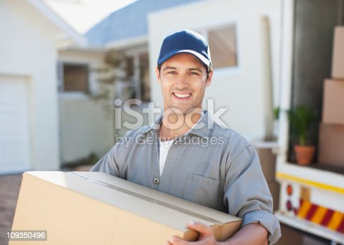 istock Smiling man carrying box from moving van 109350496