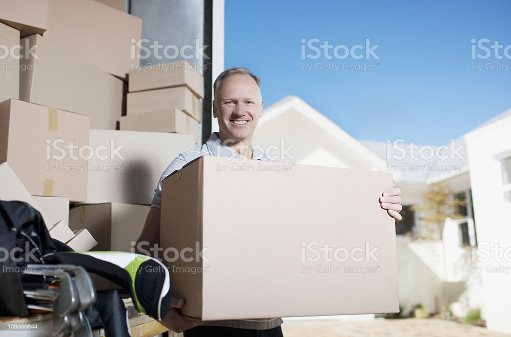 Smiling man carrying box from moving van royalty-free stock photo