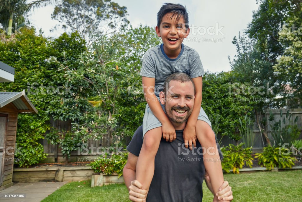 Smiling man carrying boy on shoulders at yard stock photo