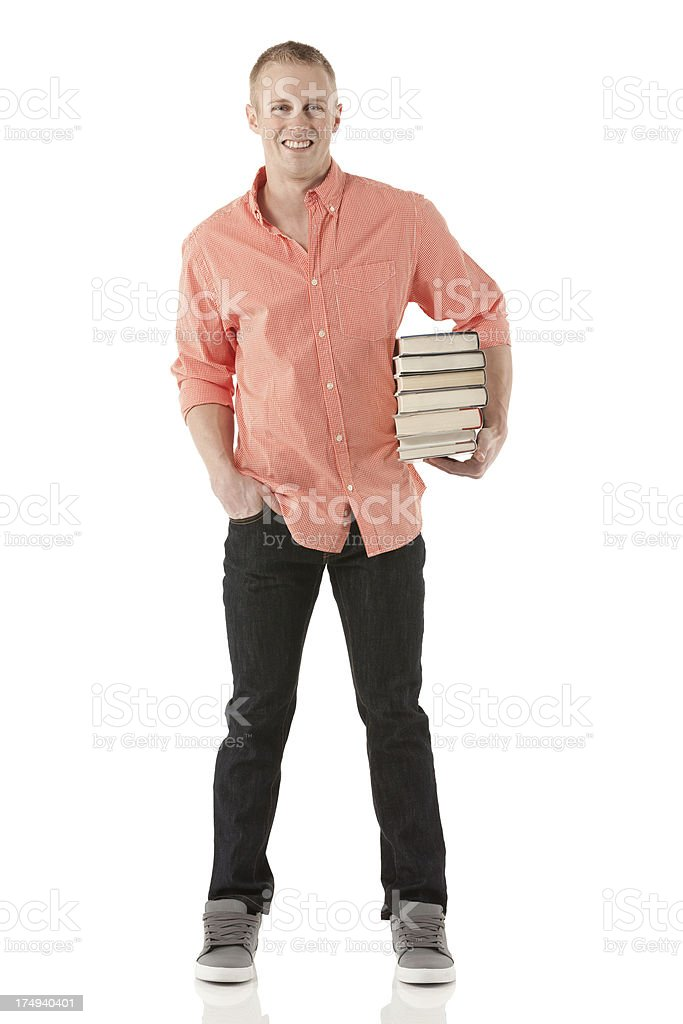 Smiling man carrying stack of books royalty-free stock photo