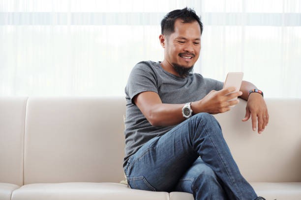 Smiling man checking his phone Filipino man sitting on sofa and reading messages in his phone filipino ethnicity stock pictures, royalty-free photos & images