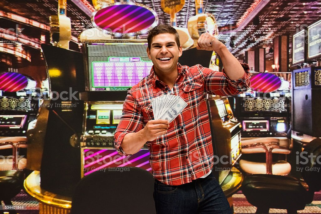 Smiling man cheering with money in casino stock photo