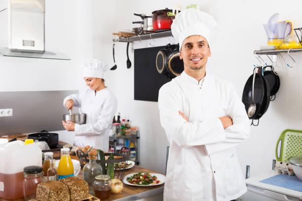 lächelnden mann chef kochen küche - chefkoch auflauf stock-fotos und bilder