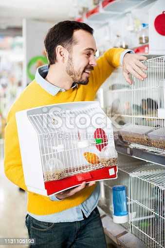 Adult handsome man choosing pretty bird for keeping in pet shop