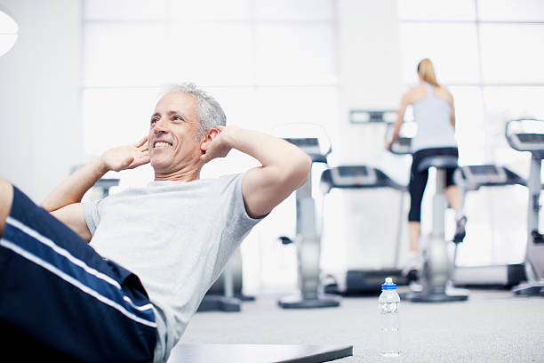 Sonriente hombre haciendo sit ups en el piso-Gimnasio - foto de stock