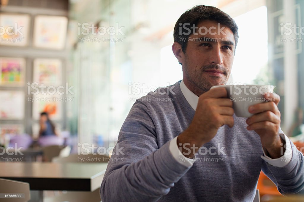 Smiling man drinking coffee in cafe royalty-free stock photo
