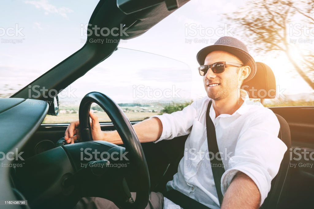 Smiling Man driving cabriolet car by province mountain road inside...
