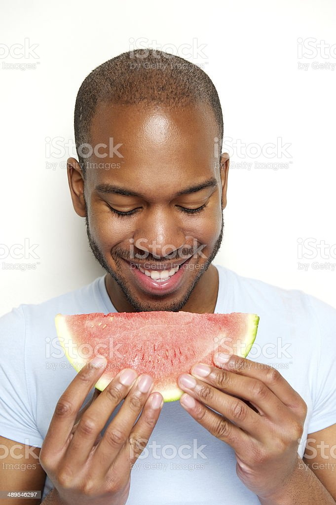 Smiling man eating watermelon stock photo
