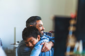 Smiling man embracing boy in bedroom. Happy father is looking away with son at home. They are spending leisure time.