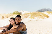 Smiling couple relaxing at beach. Happy man in looking away while embracing woman on sunny day. They are on summer vacation.