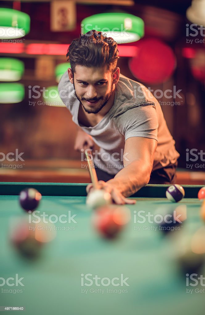 Smiling man enjoying in a pool game at pub. stock photo