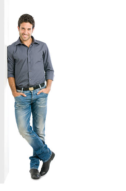 Smiling man full length Happy smiling young man leaning against white wall with copy space an the right leaning stock pictures, royalty-free photos & images