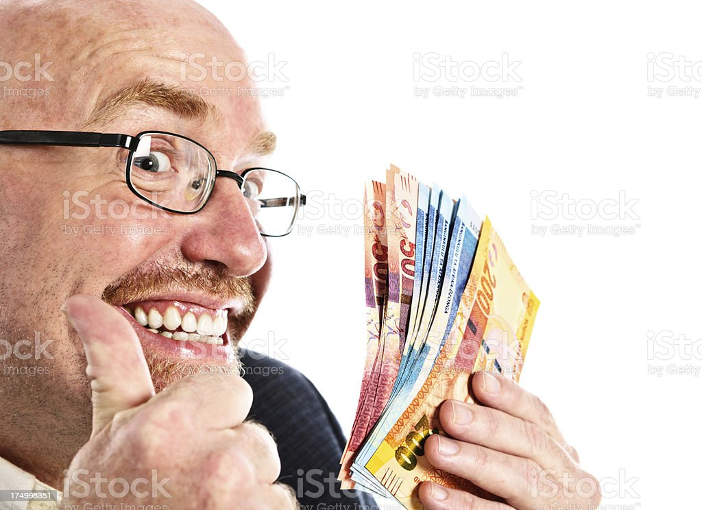 Smiling man gives thumbs up to many South African banknotes stock photo