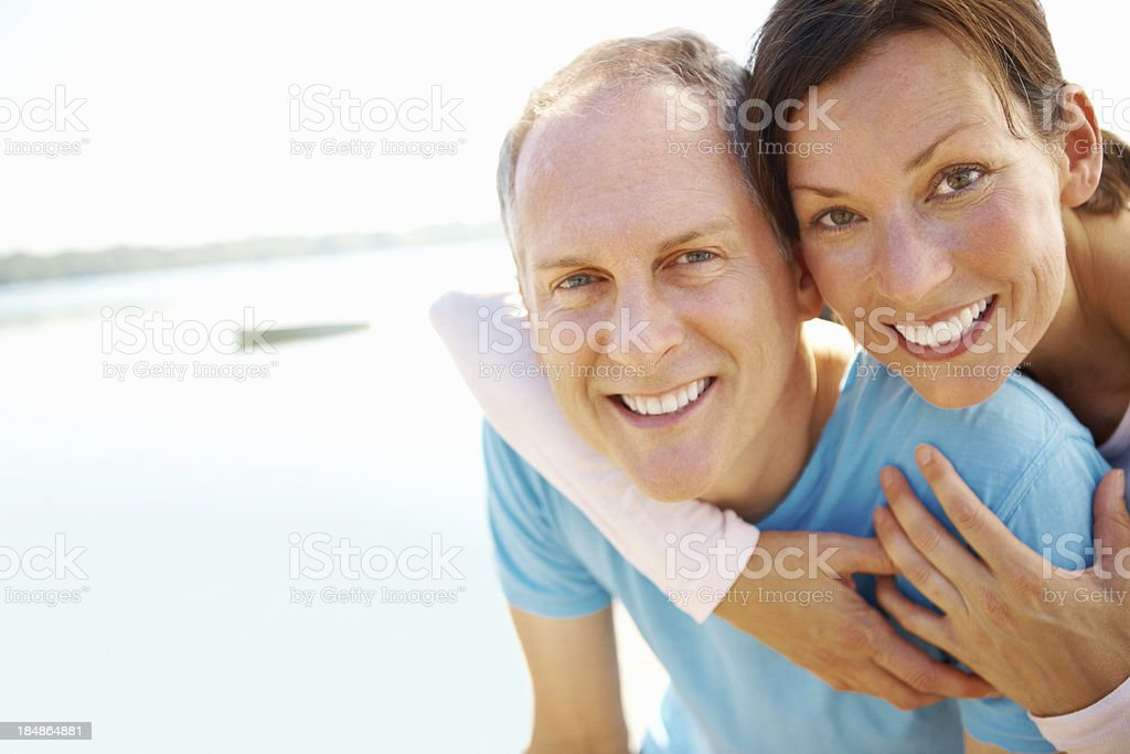 Smiling man giving woman a piggyback ride royalty-free stock photo