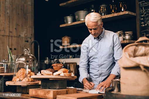 Smiling mature man going over the days receipts while standing behind the counter of his trendy cafe