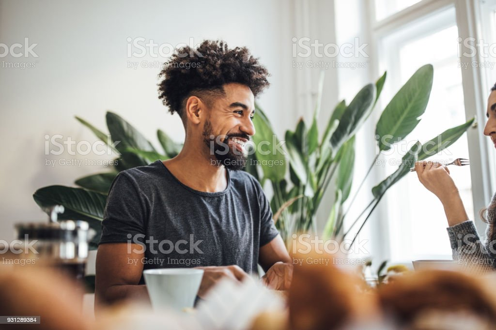 Smiling man having breakfast with woman at home royalty-free stock photo