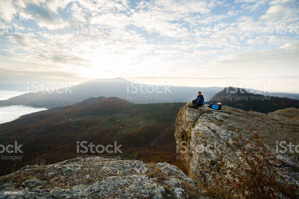 Alpinista de homem sorridente com mochila, localização e relaxante no topo da montanha e olhar amarelo outono paisagem pôr do sol sobre as nuvens - foto de acervo