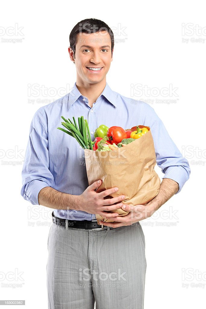 Smiling man holding bag filled with fruits and vegetables royalty-free stock photo