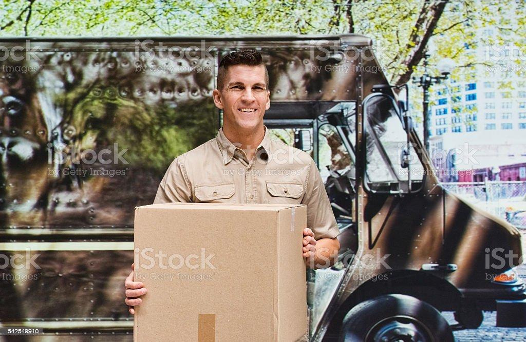 Smiling man holding box outdoors stock photo