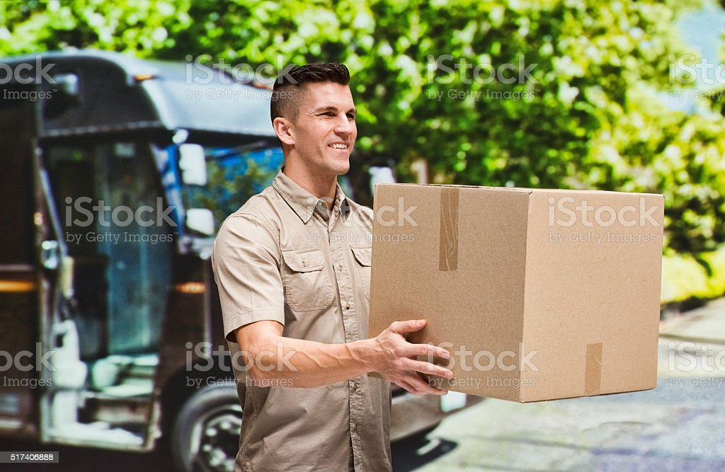 Smiling man holding box stock photo